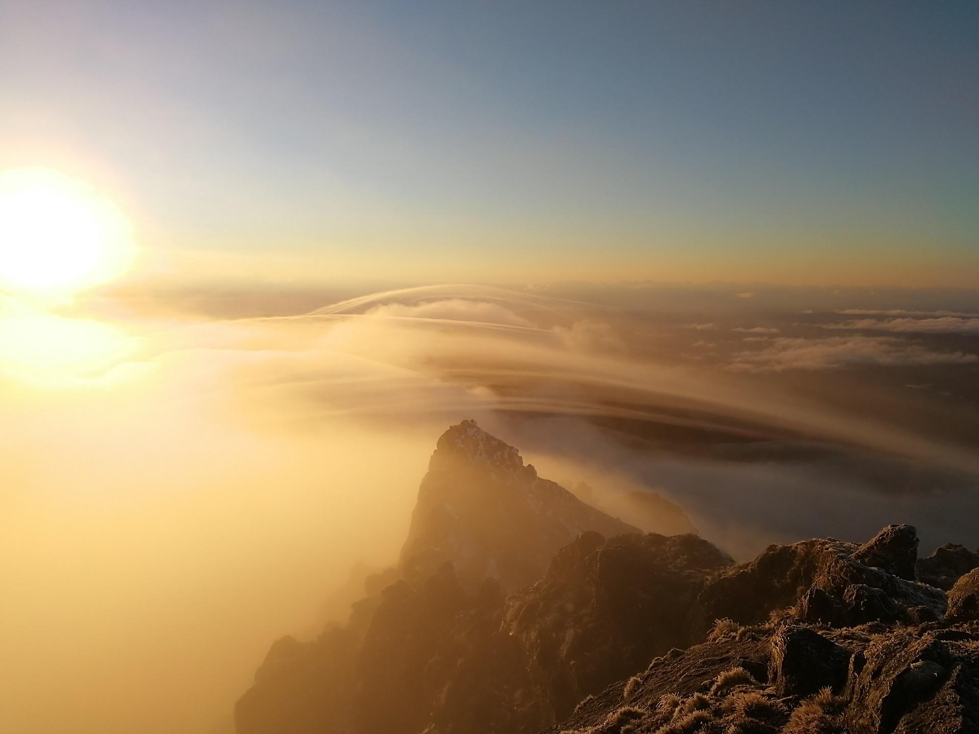 Slunce prostupuje ranní mlhou na Hikurangi