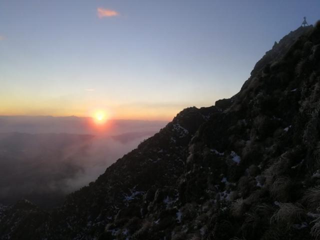 První východ slunce a první sluneční paprsky na obzoru za horou Hikurangi