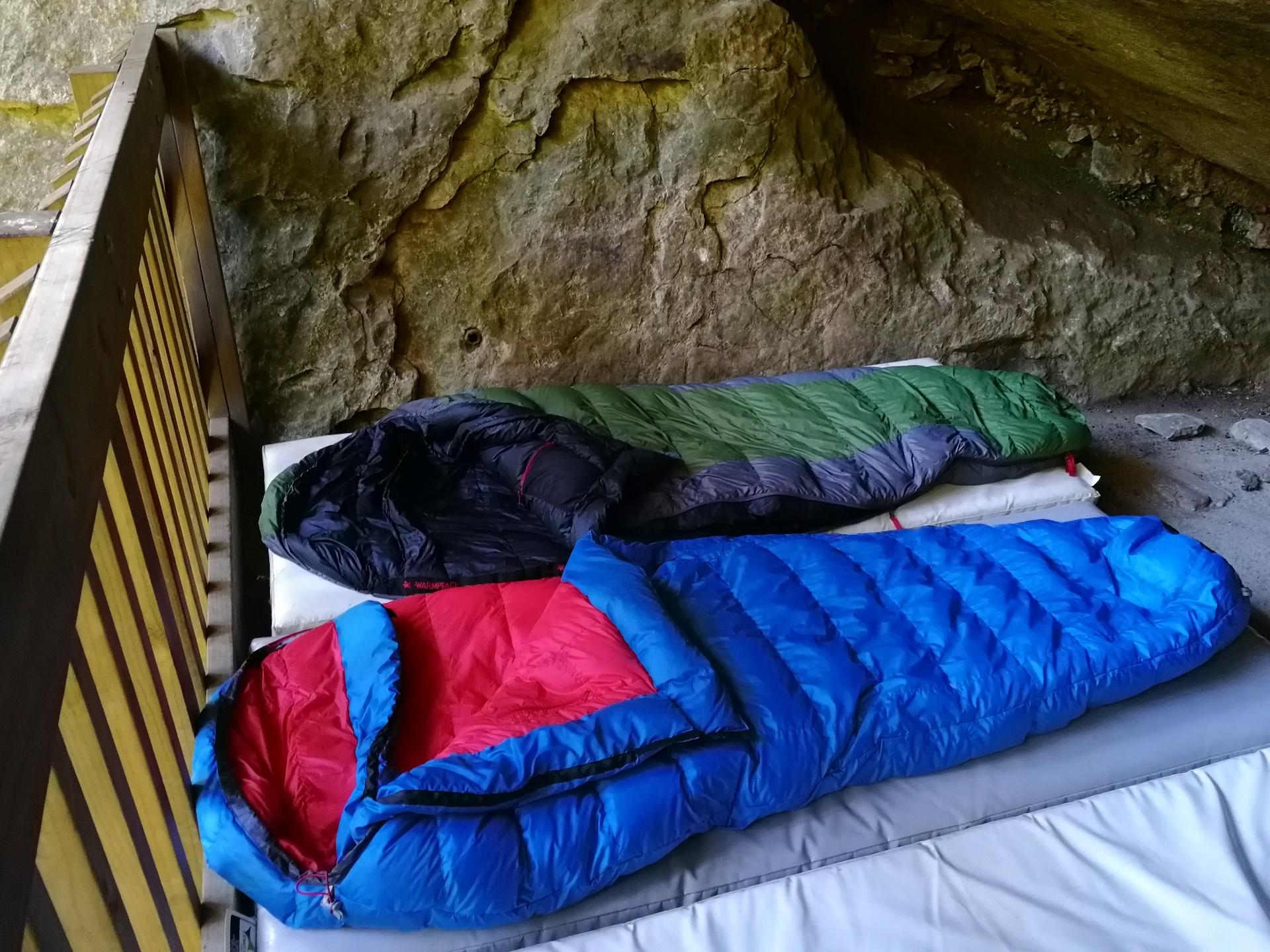 Rozložené otevřené třísezónní péřové spacáka Warmpeace a Sir Joseph ve skalním bivaku