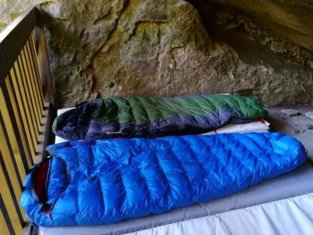 Rozložené péřové spacáky Warmpeace a Sir Joseph ve skalním bivaku