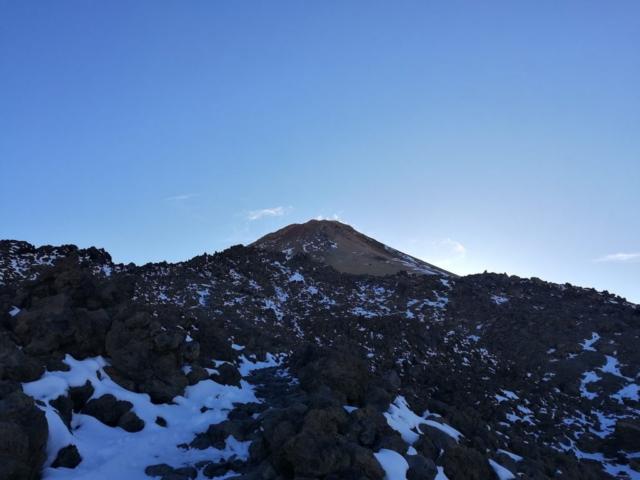 Vrchol sopky Pico del Teide, pod sopkou sopečné balvany se zbytky sněhu