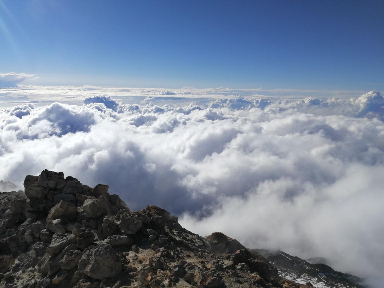 Pohled z vrcholu Teide, okraj sopky a vzadu modrá obloha a oblaka